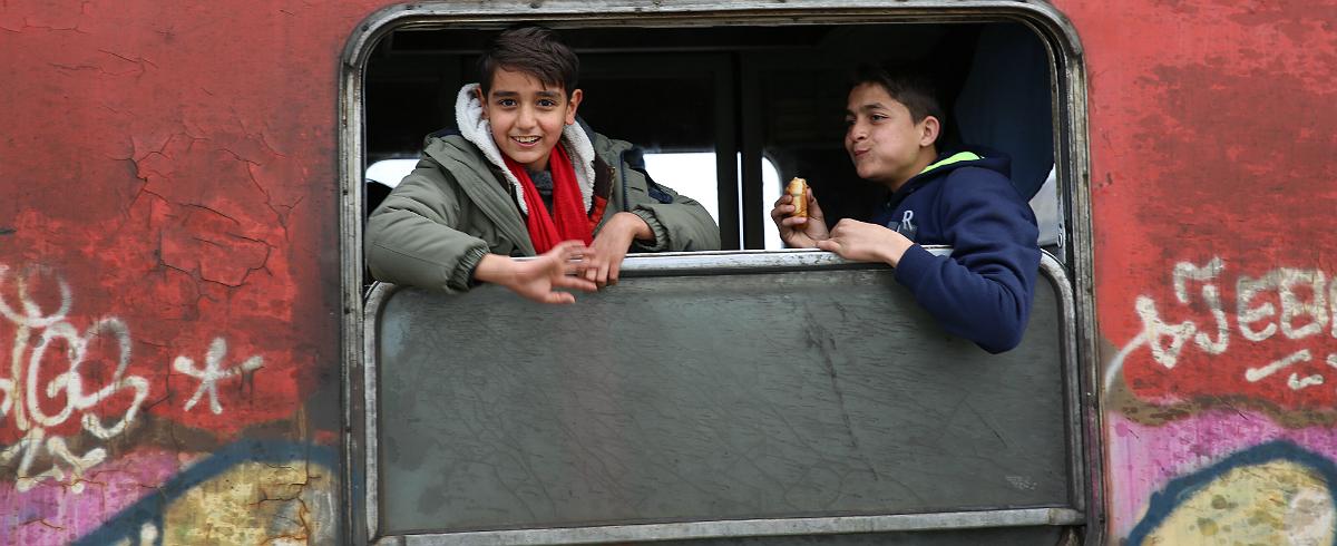 Dos niños migrantes en un tren en Tabanovtse en la ex República Yugoslava de Macedonia. Foto de las Naciones Unidas